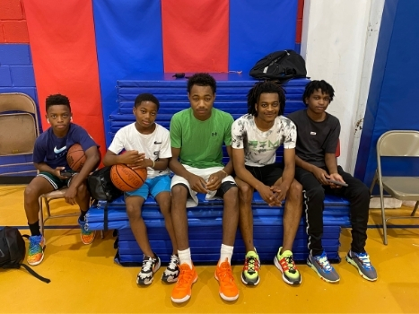 a group of young boys and men sitting together in the gym