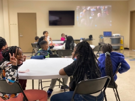 young adults sit together at round tables at the palw