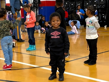 a young boy smiles during an event at the gym
