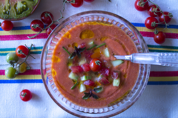 A Blender Base with ripe Summer Tomatoes, Cucumbers and Herbs