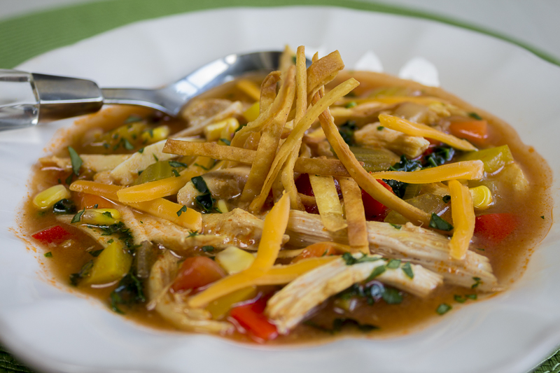 Top the soup with grated sharp cheese, tortilla strips and fresh herbs