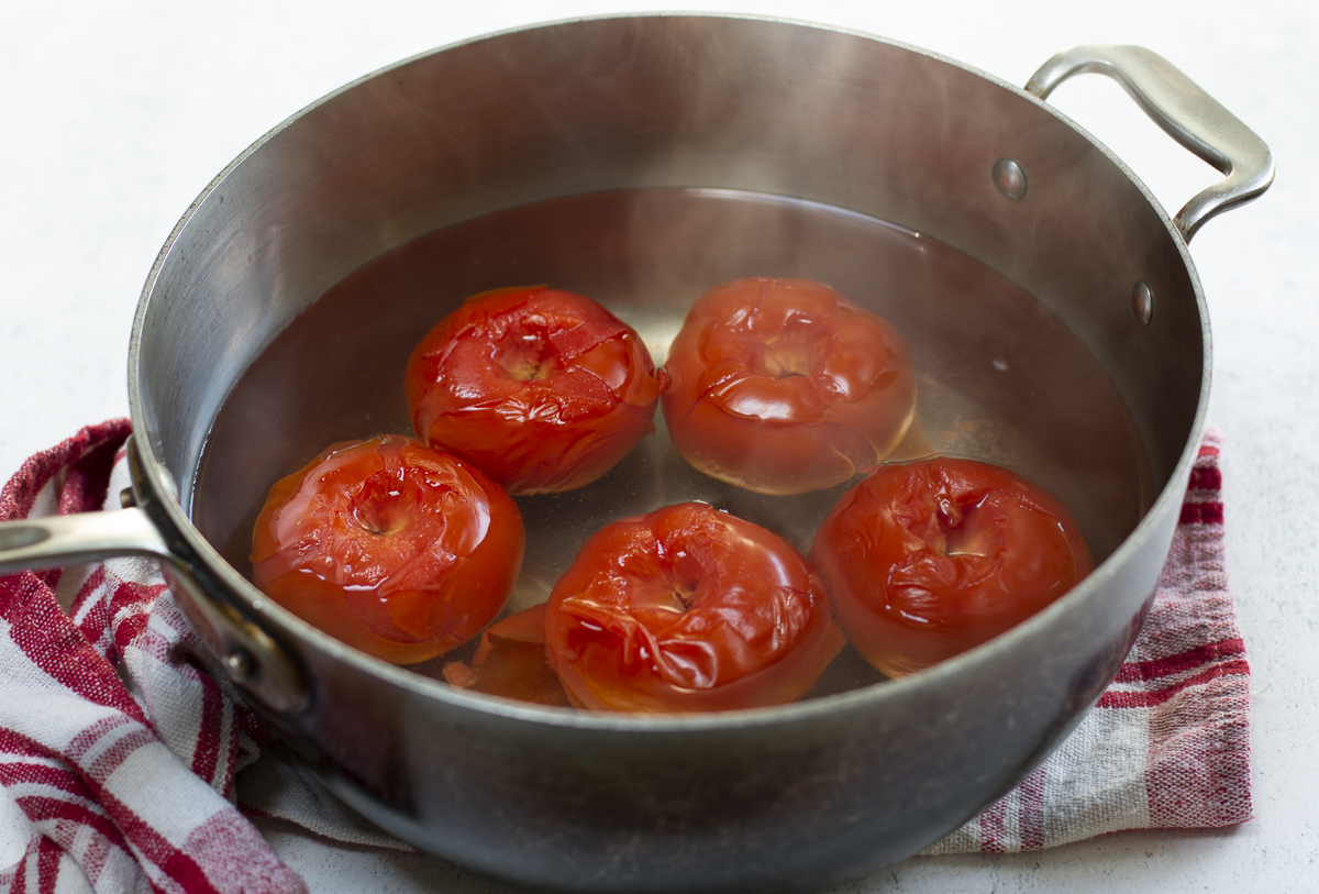 Poach the tomatoes in boiling water until the skins wrinkle and loosen. Cool, peel and chop