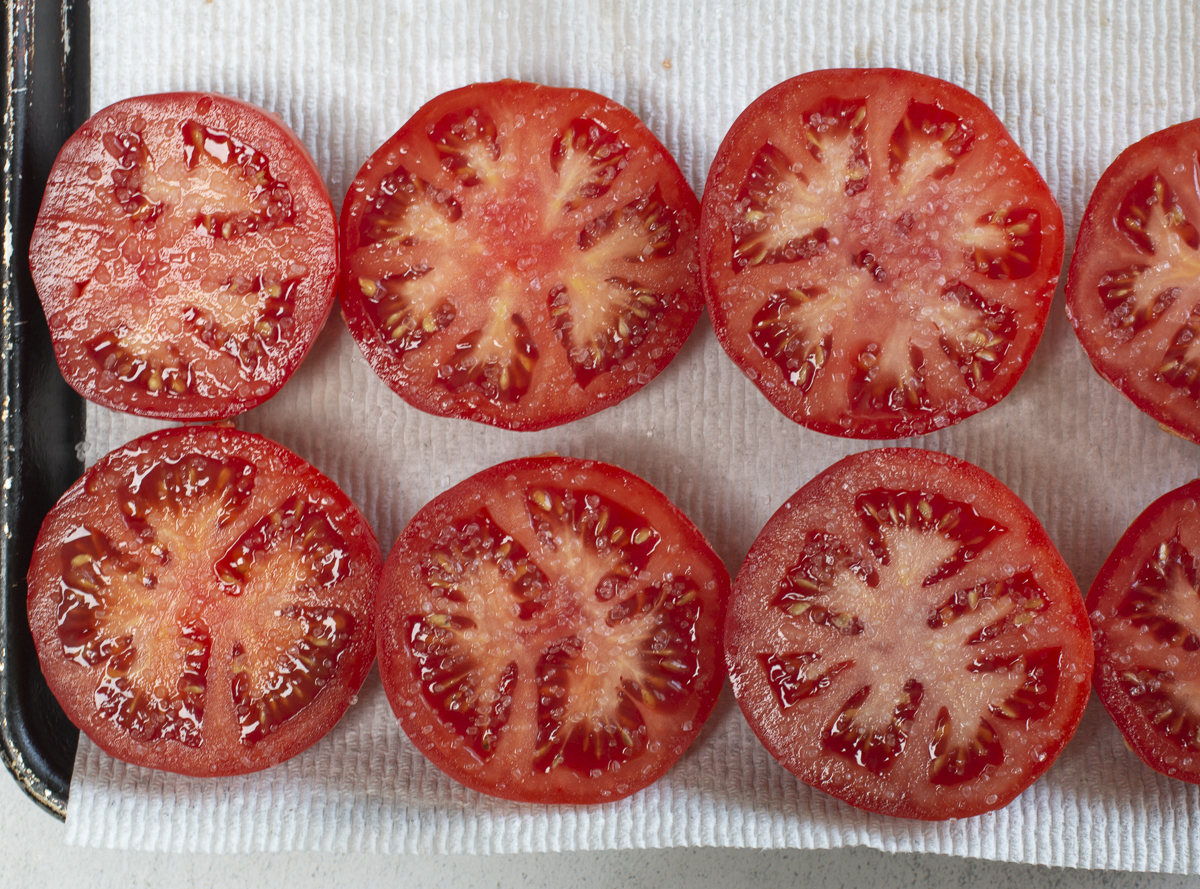 Salted tomatoes resting on paper towels