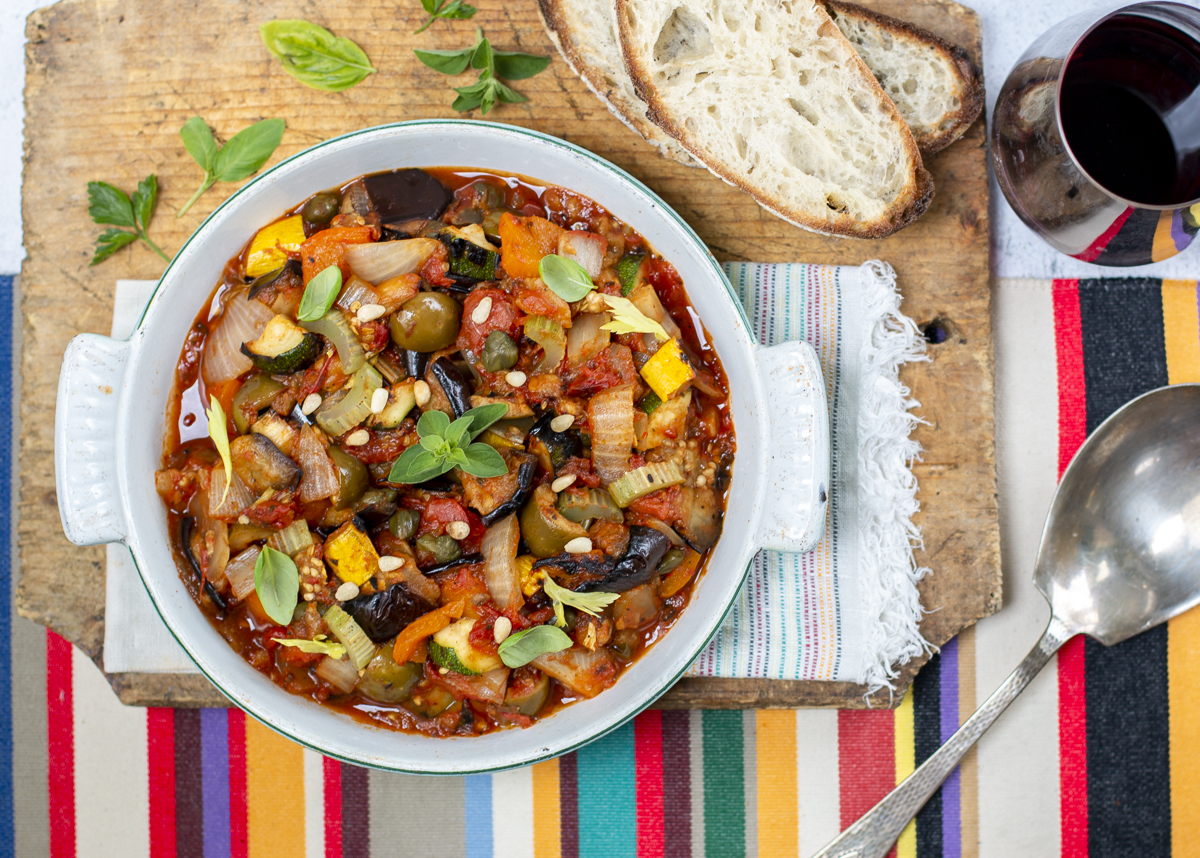 Grilled caponata in a vintage baking dish with oregano and pine nuts