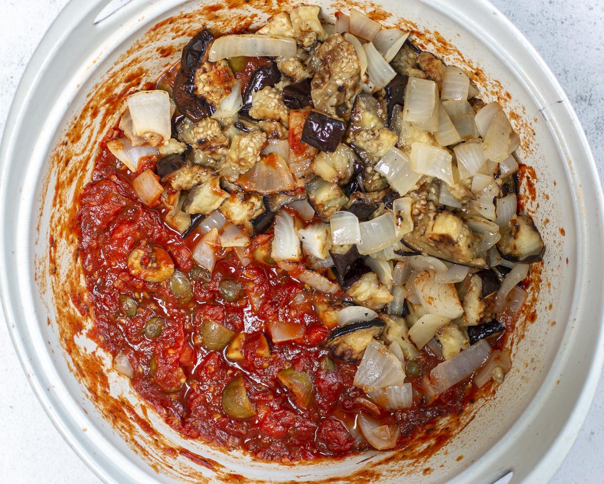 Adding eggplant and onions to the caponata stew