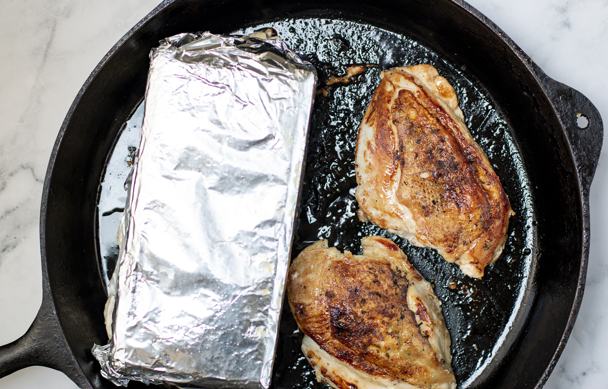 chicken breasts in a cast iron skillet with skin side down using two bricks a weights