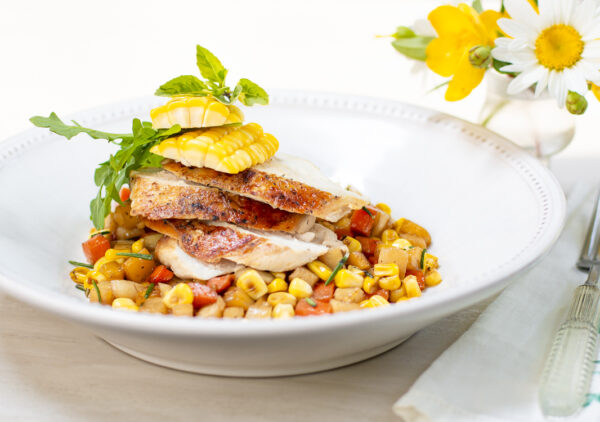 Sliced brick chicken breast on a Summer vegetable ragout in white bowl