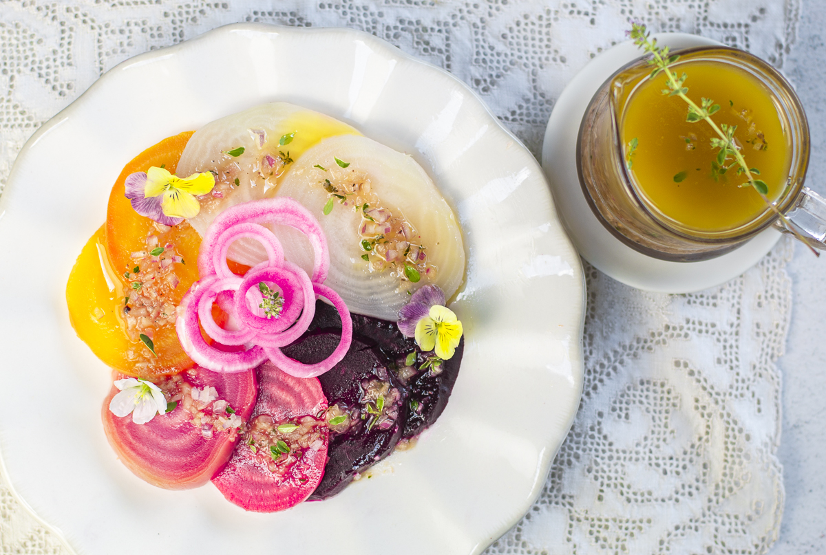 Four different colors of steamed beets with pickled onions and shallot-thyme vinaigrette in a bowl