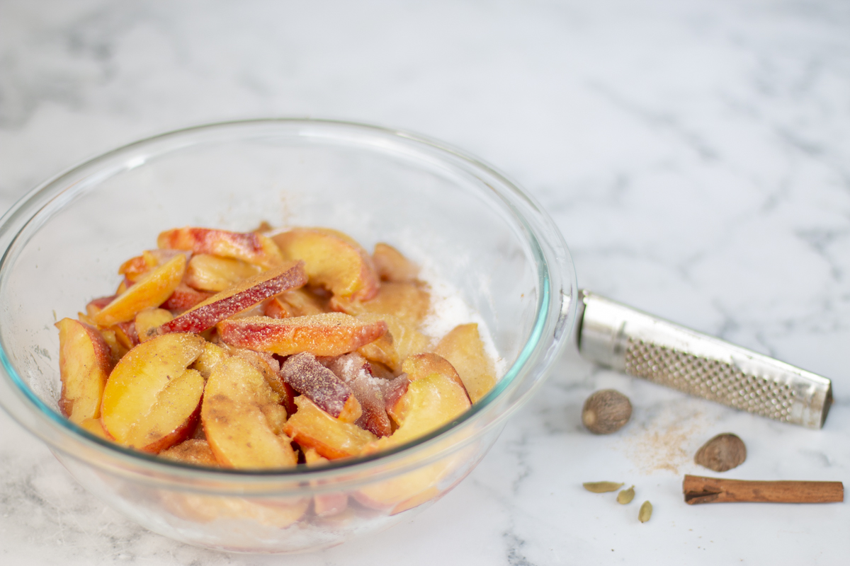Sliced peaches in a bowl for pie with nutmeg, cinnamon and cardamom