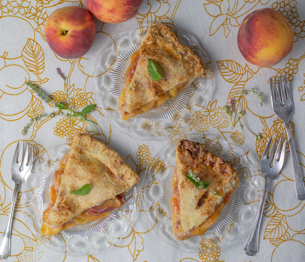 Three slices of Perfect Peach Pie with Whipped Coconut Cream & Basil Syrup on a vintage linen