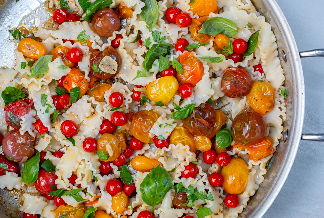 """Tossing the heirloom cherry tomato """"sauce"""" with the pasta ribbons"""