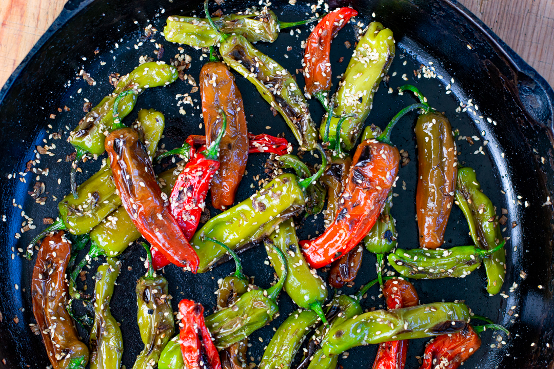 Close up Multi- Colored Shishito Peppers in a cast iron
