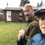 man and woman point to a moose in the back yard.