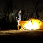 Man by tent at night