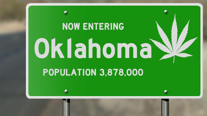 "Illustration showing ""now entering Oklahoma"" highway sign with marijuana leaf"