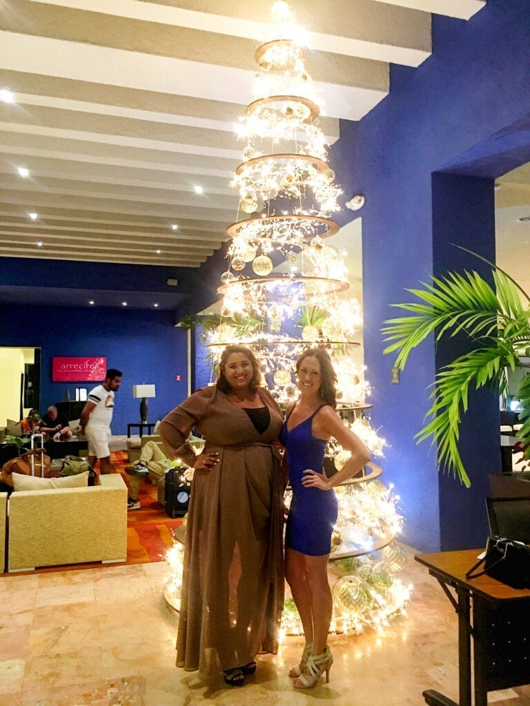 Girls posing and smiling in dresses in front of a Christmas tree in Cancun