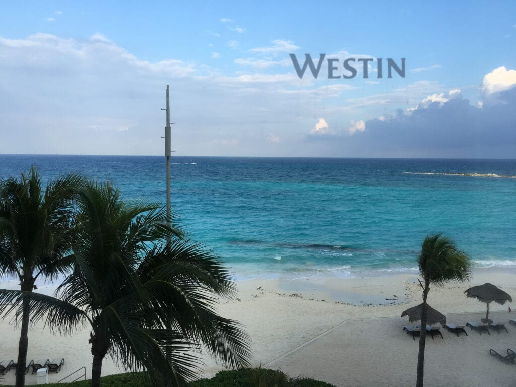 """View of ocean from hotel room with """"Westin"""" on the window"""