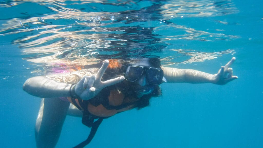 girl snorkeling in Cabo San Lucas, Mexico peace sign water