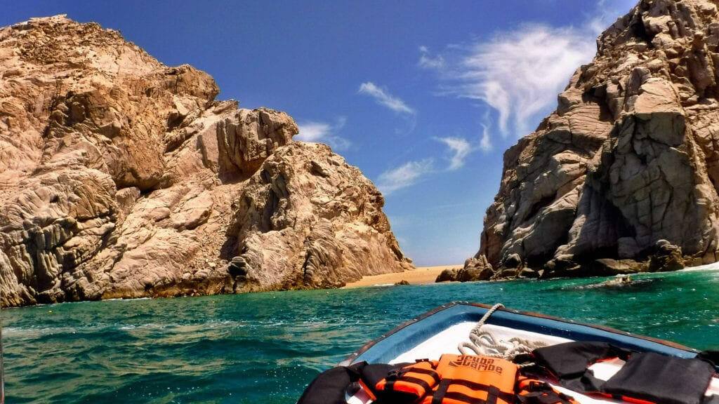 boat approaching rock formations in the ocean Cabo San Lucas, Mexico