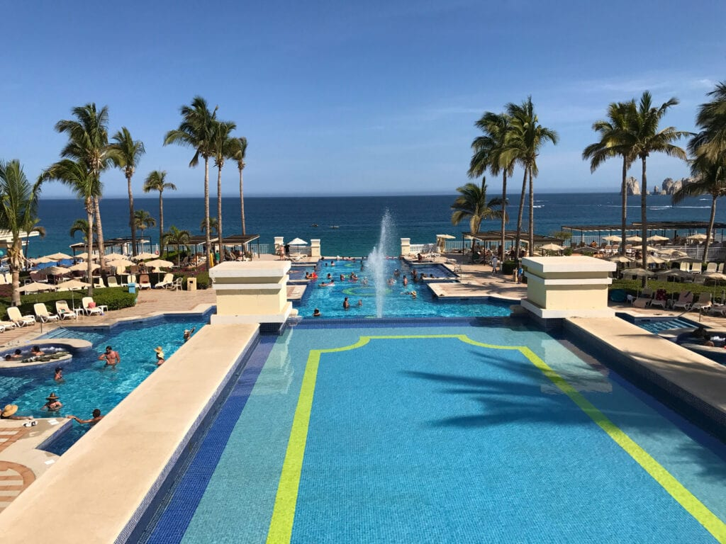 view of the pool with waterfall and palm trees against the sky at the Rui Hotel and Resort, Cabo San Lucas, Mexico