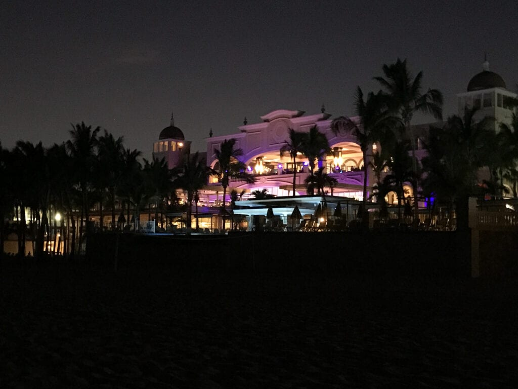 Rui Hotel and resort in Cabo San Lucas, Mexico. Night with resort illuminated in the background against palm trees