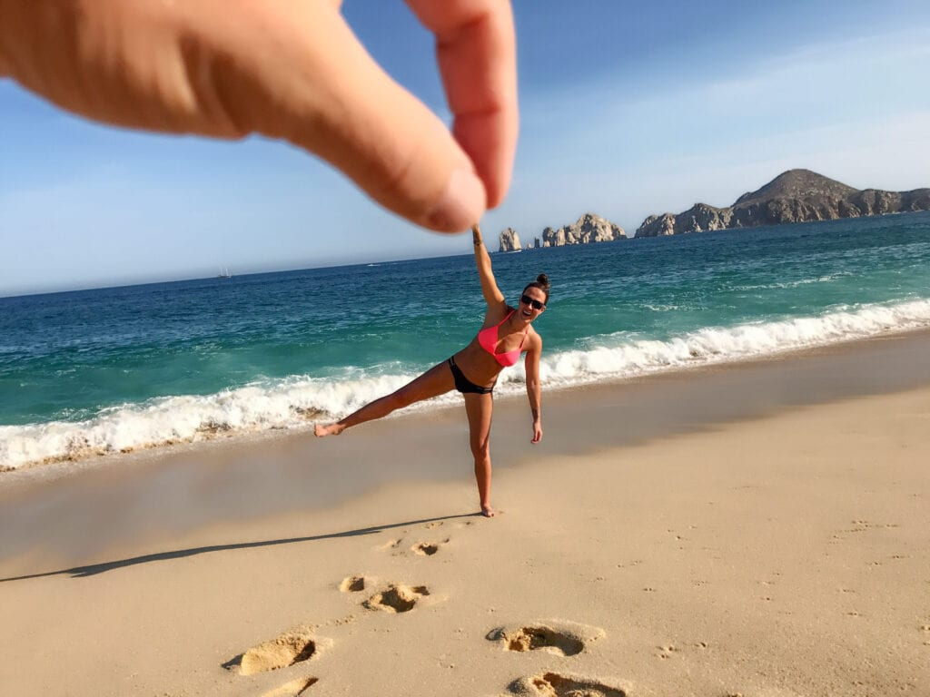 creative beach shot, girl being held up by finger at the Rui Hotel and Resort, Cabo San Lucas, Mexico