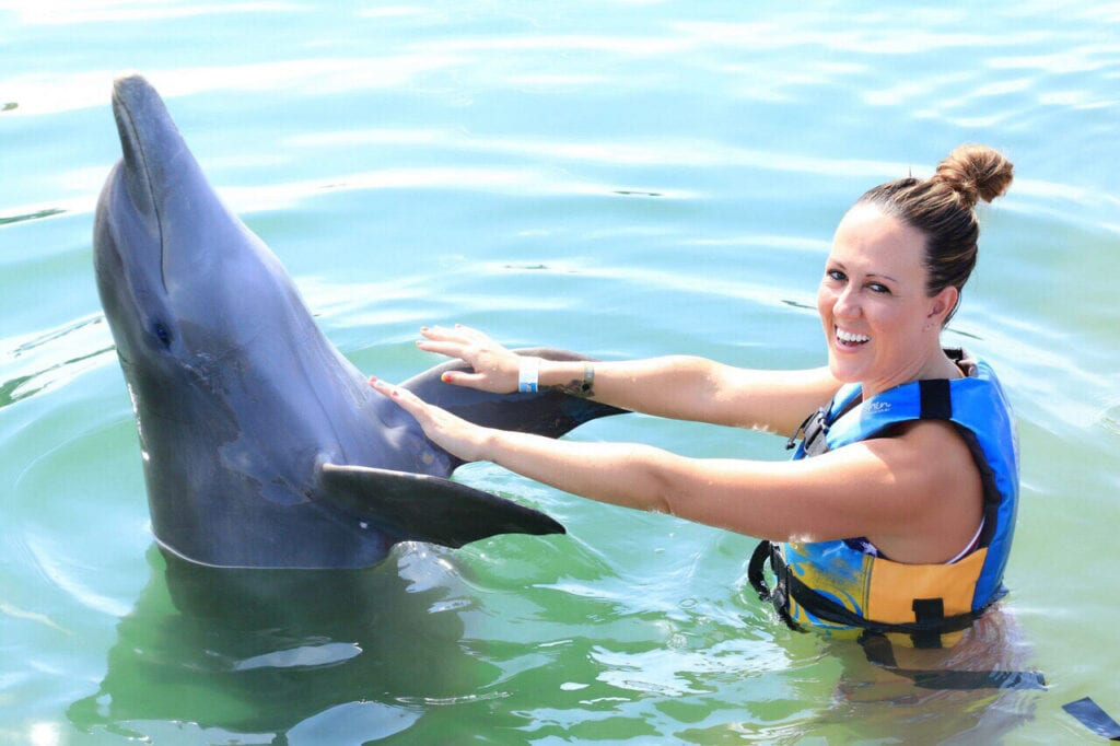 girl touching dolphin and laughing in Cabo San Lucas, Mexico