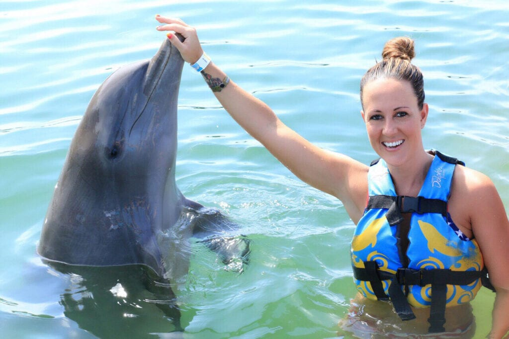 girl posing with dolphin and touching nose in Cabo San Lucas, Mexico