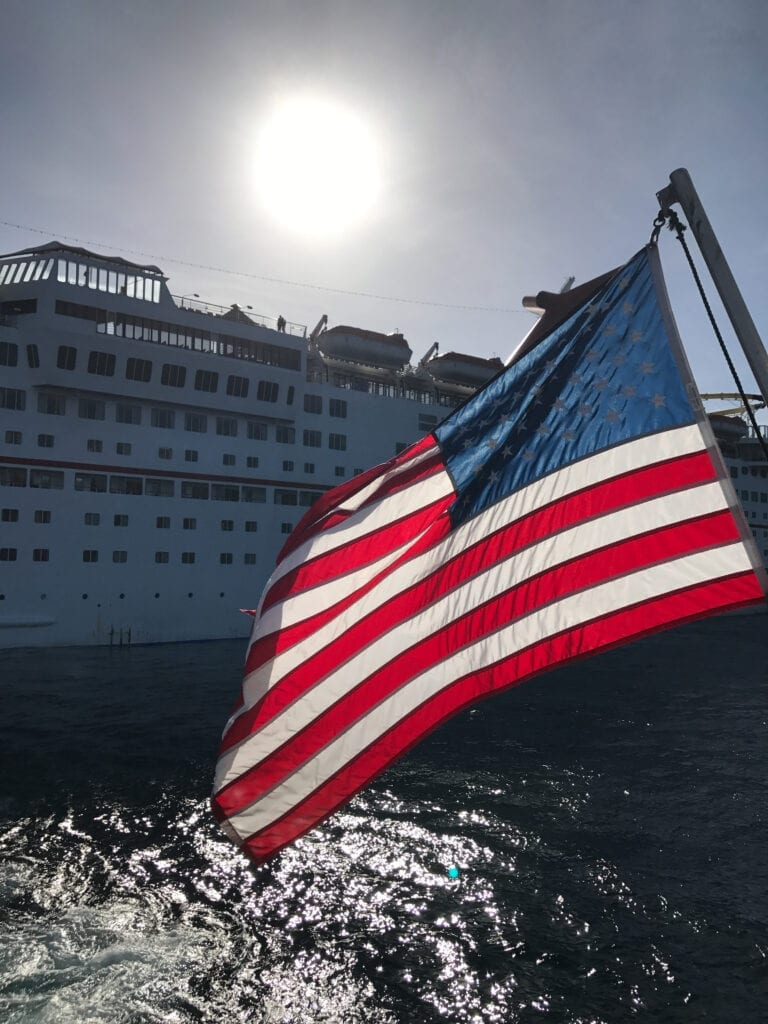 View of the cruise ship from the water with the american flag waving in the wind