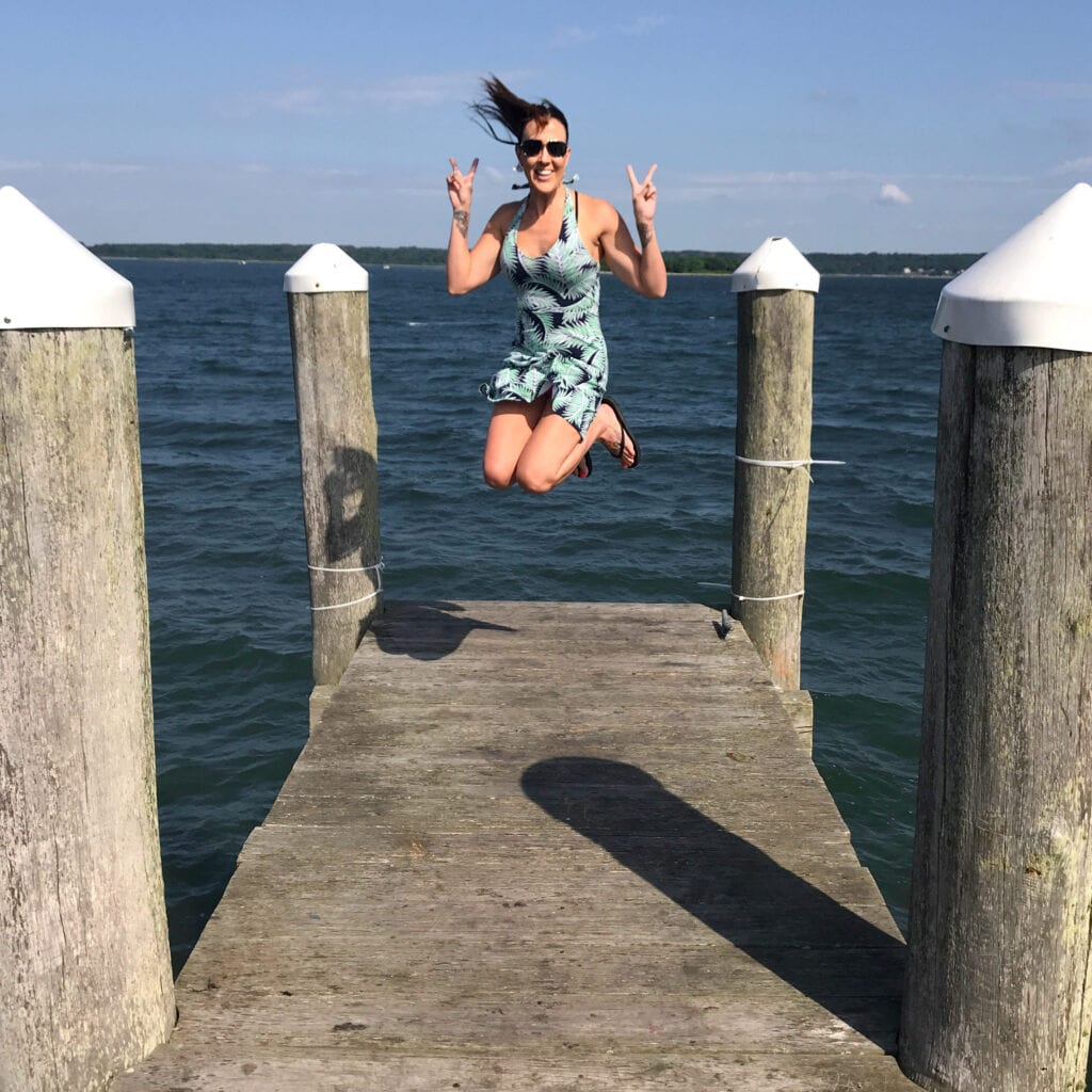 Girl on dock jumping with peace sign overlooking the ocean