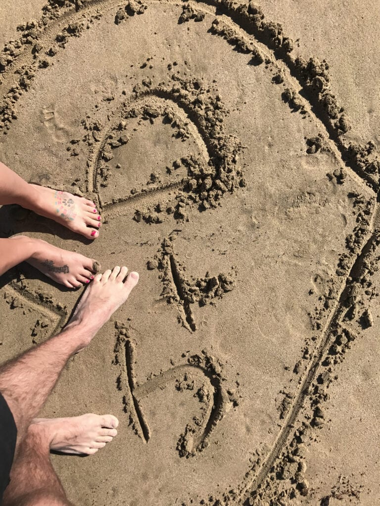 """""""J+D"""" written in the sand with feet on the beach"""