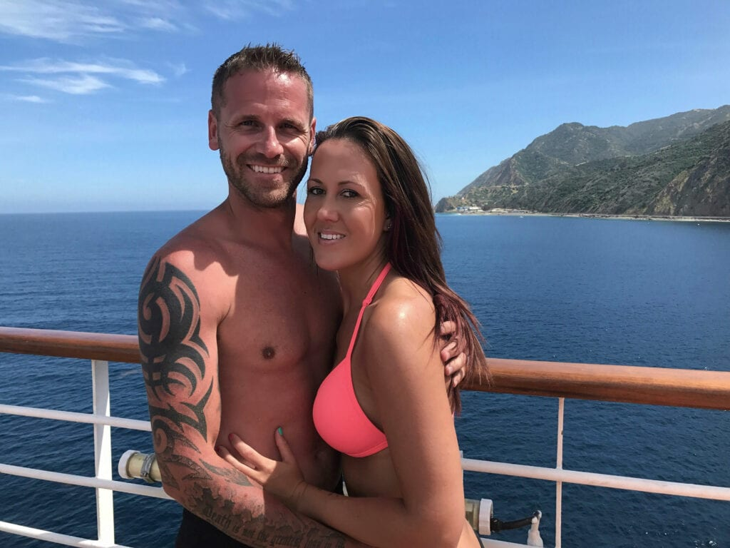 Man and woman smiling and hugging on cruise ship overlooking the ocean