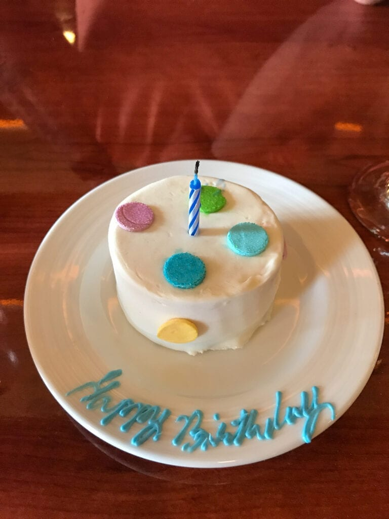 """Polka dot decorated birthday cake with one candle and  """"happy birthday"""" written in icing"""