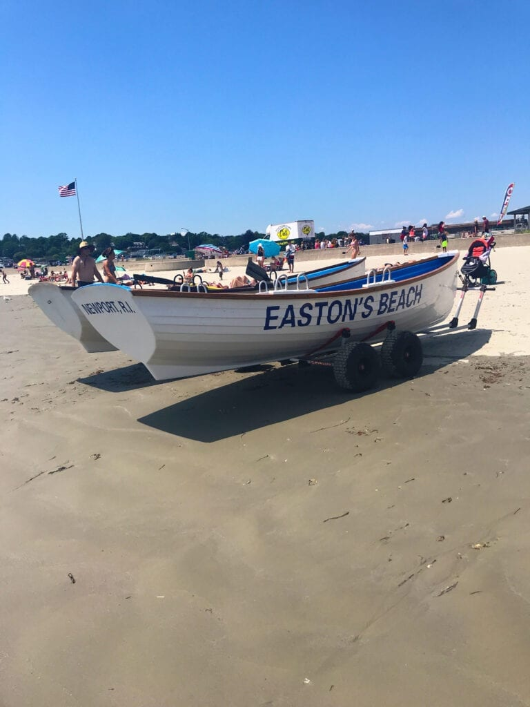 """Boats on shore that read """"Easton's Beach"""" on the side in Newport Rhode Island"""