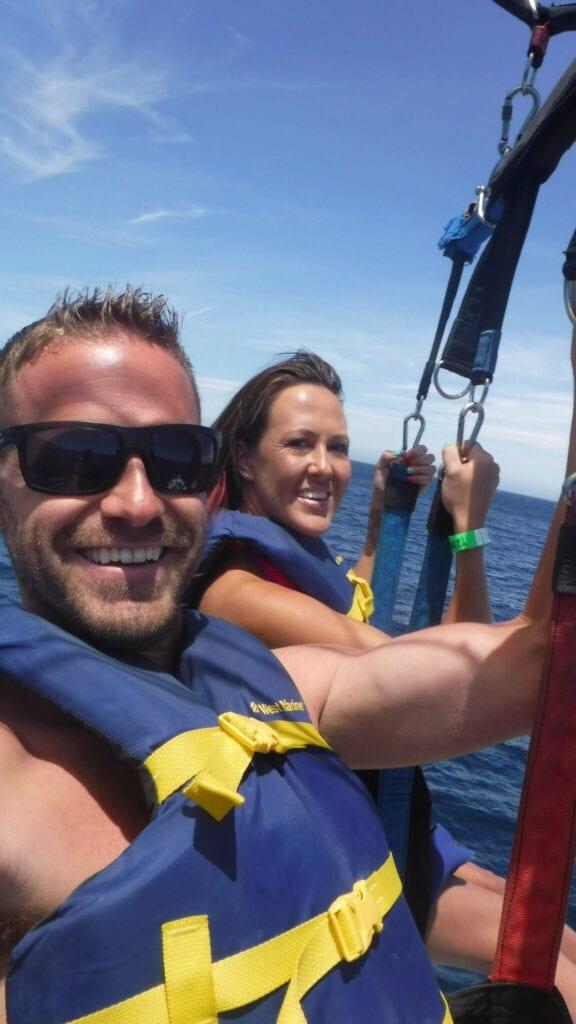 Man and women smiling while parasailing