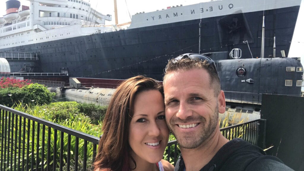 Man and woman standing in front of cruise ship in Long Beach, Caliiornia