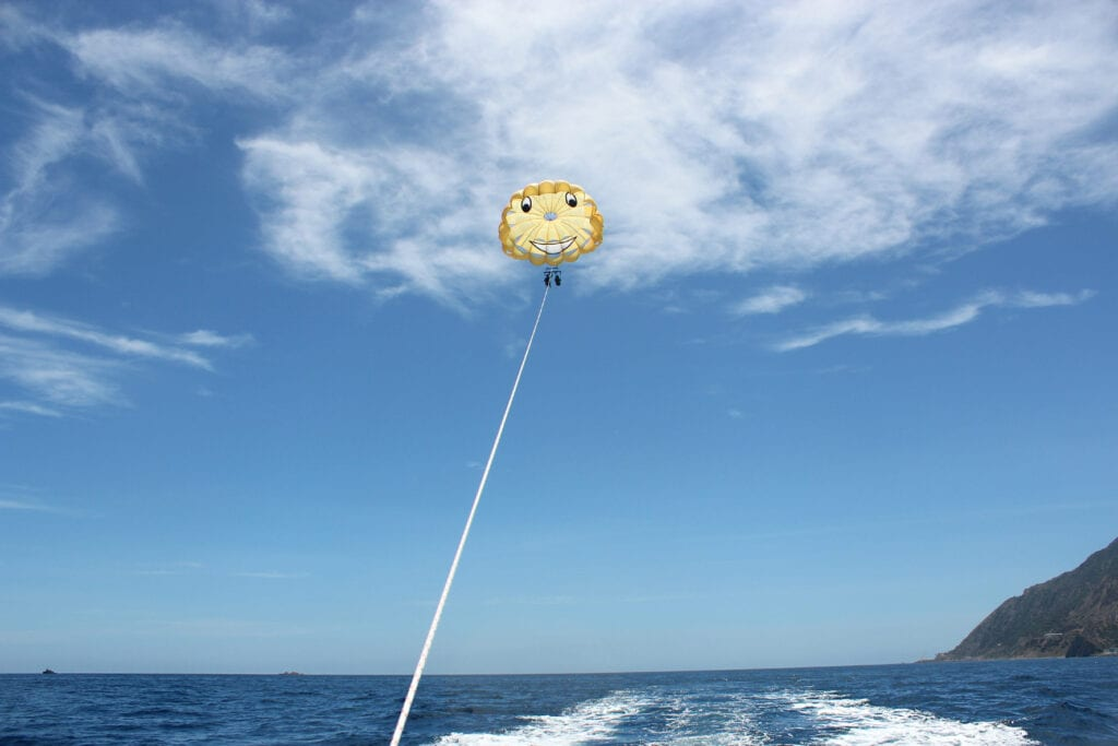 distant photo of parasailing, smiley face parachute