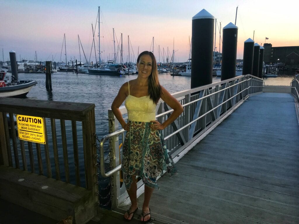 Girl standing on bridge at Newport Harbor with sunset and boats on the water