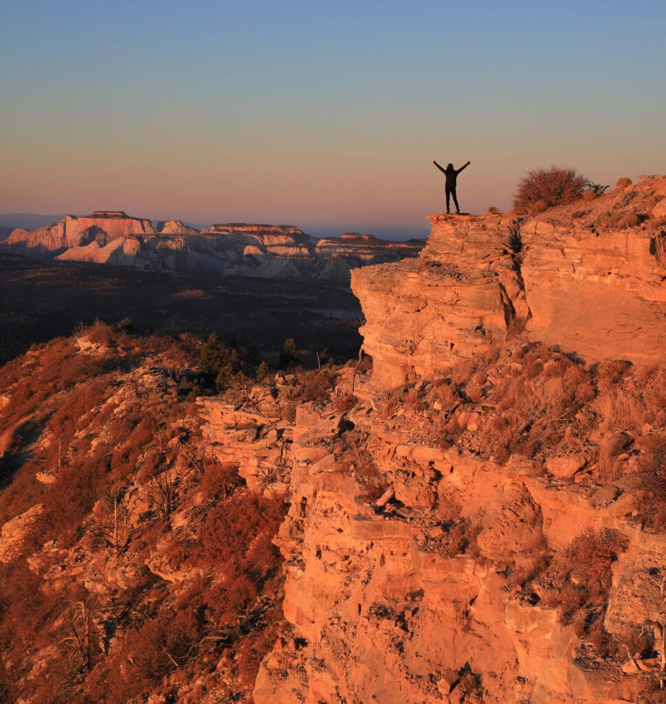 Girl standing on mountain ledge Zion