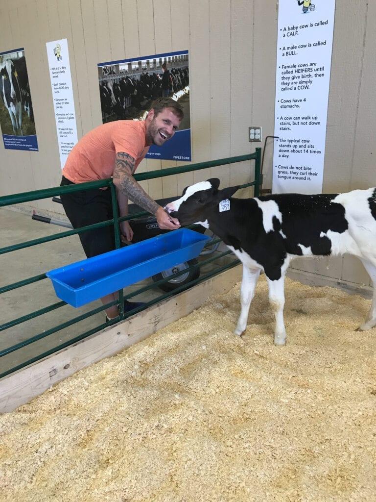 man feeding baby cow Sioux Falls Empire Fair