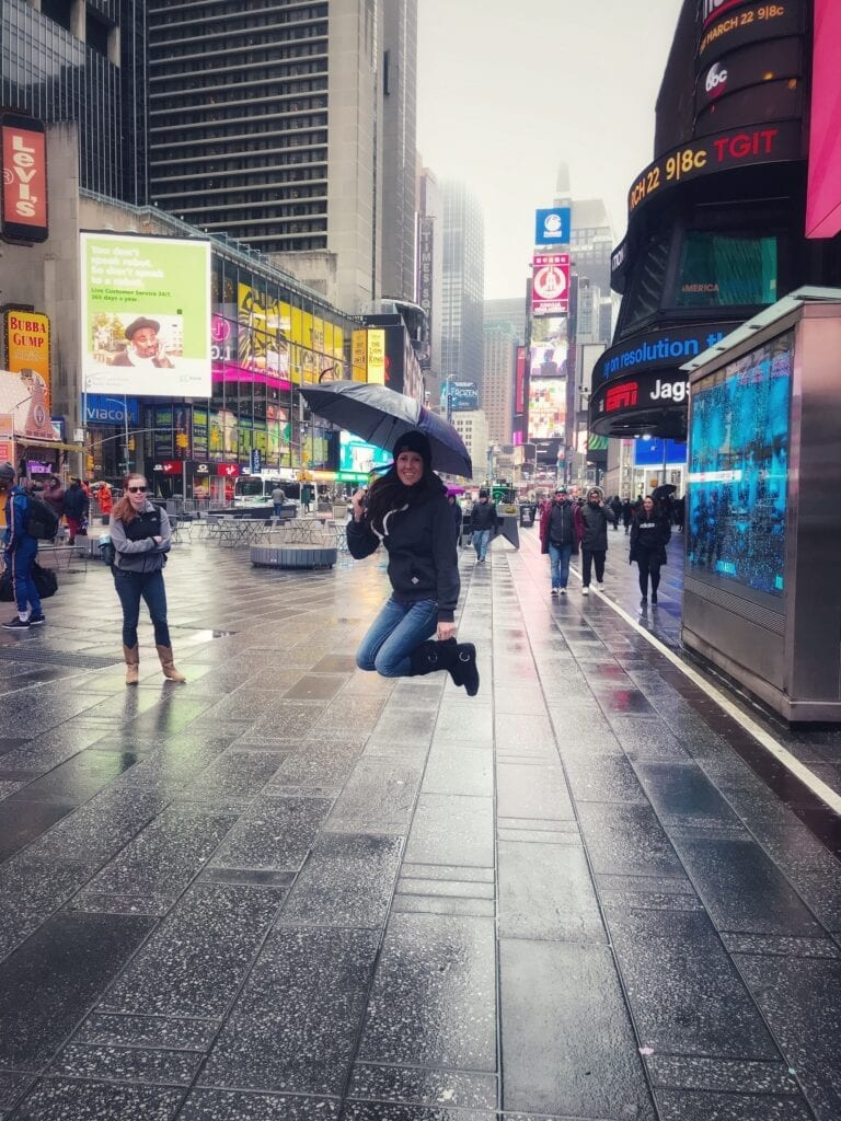 Girl jumping in Times Square with umbrella in the rain, New York