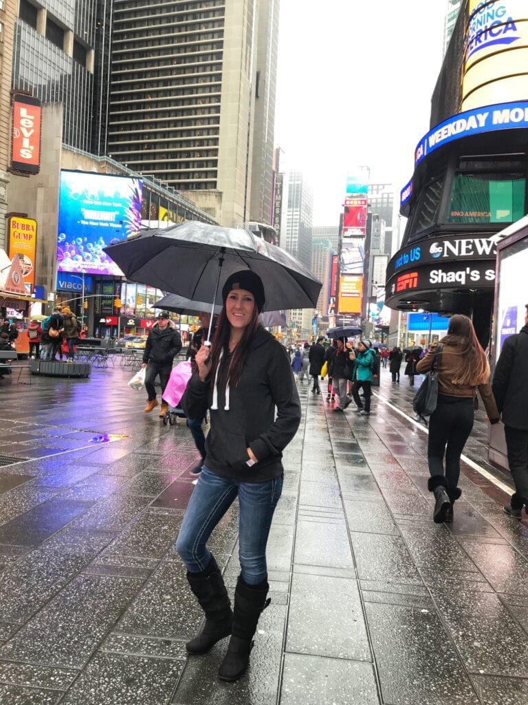 Girl standing in Times Square with umbrella in the rain, New York