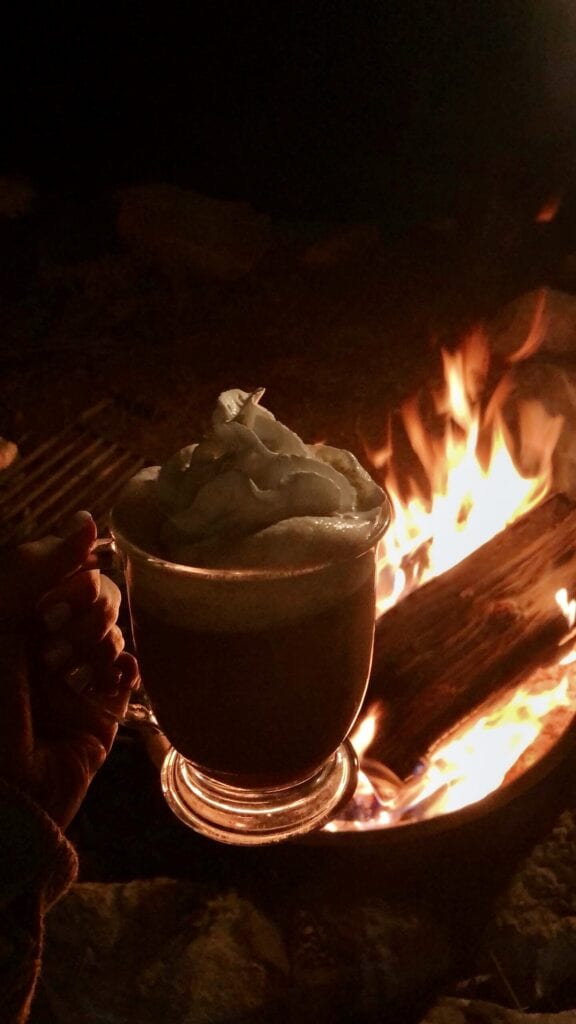 cocoa with whip cream next to a fire