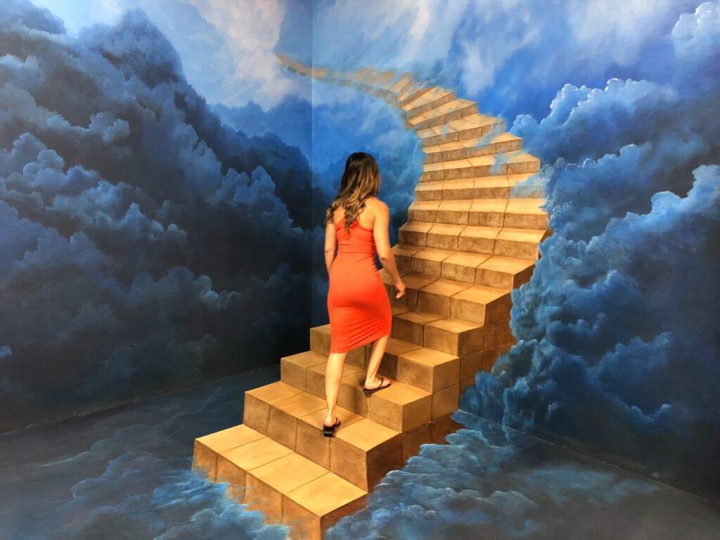 girl walking up stairs trick art
