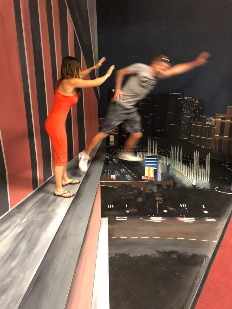 woman pushing man off cliff trick art museum