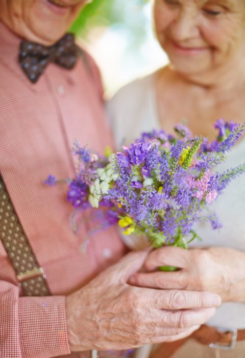 Elderly couple holding flowers in their hands