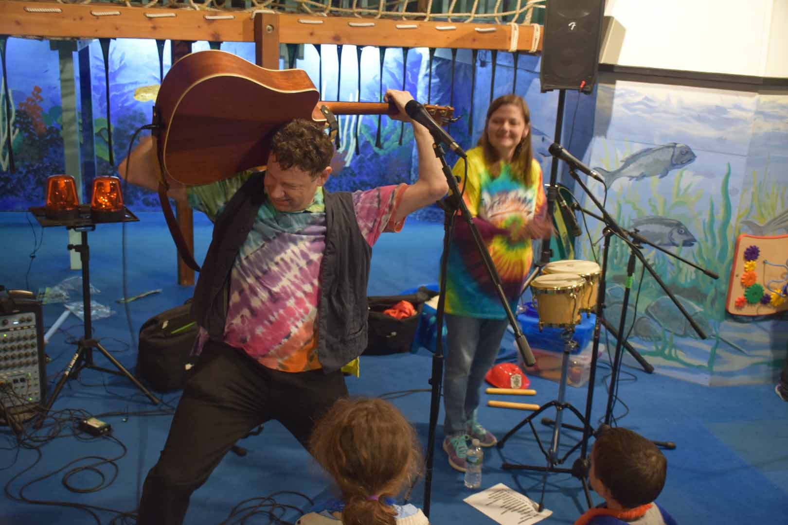 Jason Didner and the Jungle Gym Jam acoustic duo. Jersey Jason has his guitar behind his head as Awesome Amy keeps the beat.