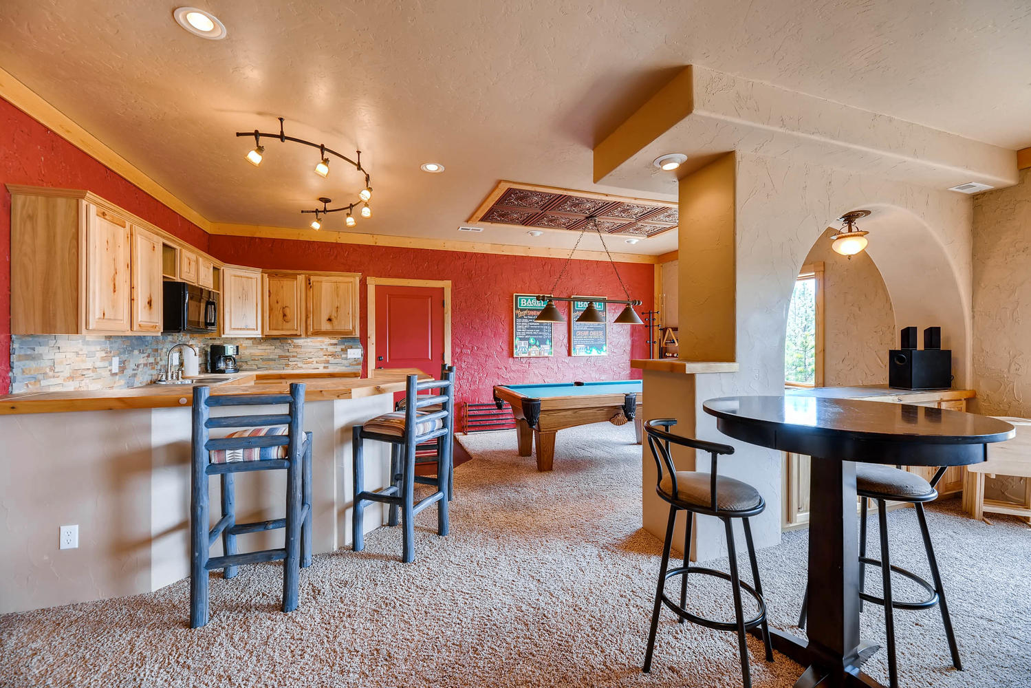 A pub table and kitchen bar create plenty of seating for enjoying some game time snacks.