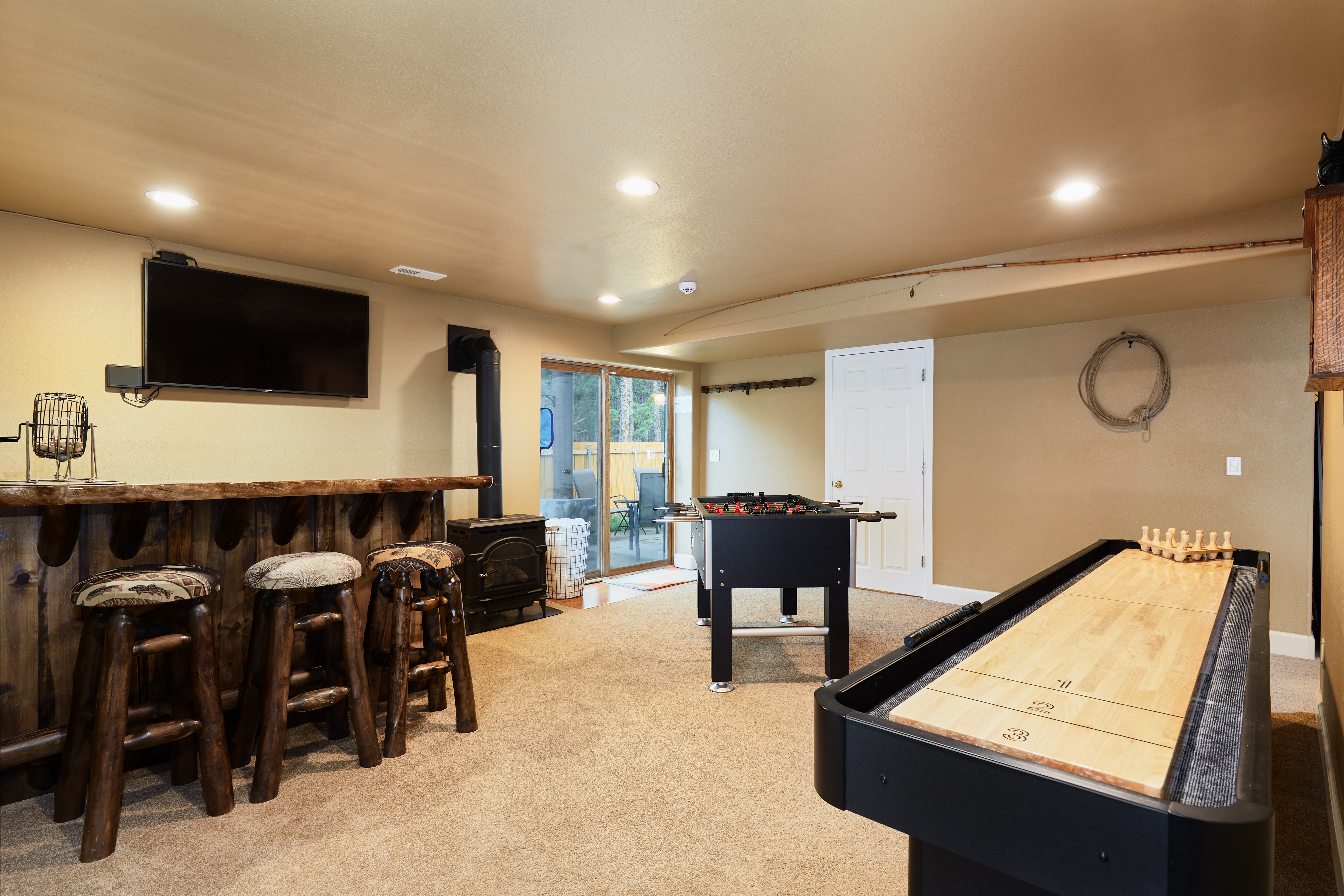 The basement is home to the game room with bar, TV, shuffleboard and foosball table.