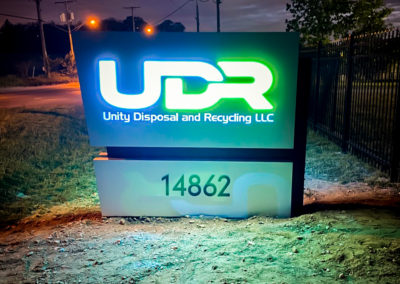 Night view. Illuminated Monument sign that reads UDR Unity Disposal and Recycling LLC